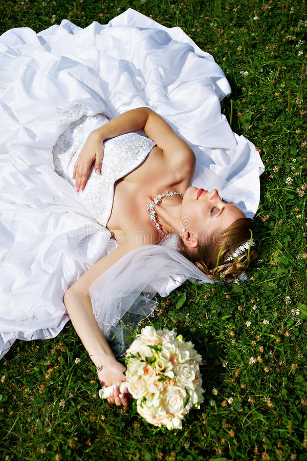 Happy sleeping bride are on grass royalty free stock photos