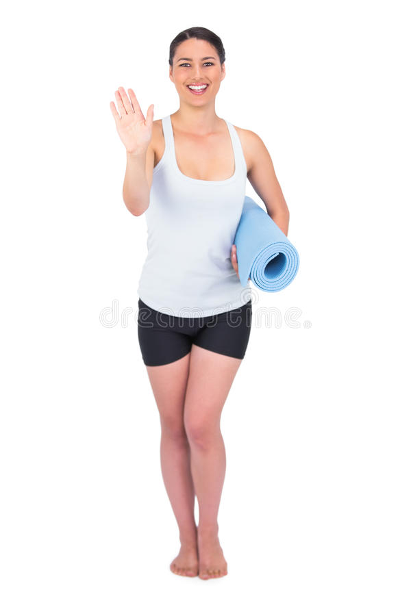 Happy slender model holding her rolled up mat royalty free stock photography