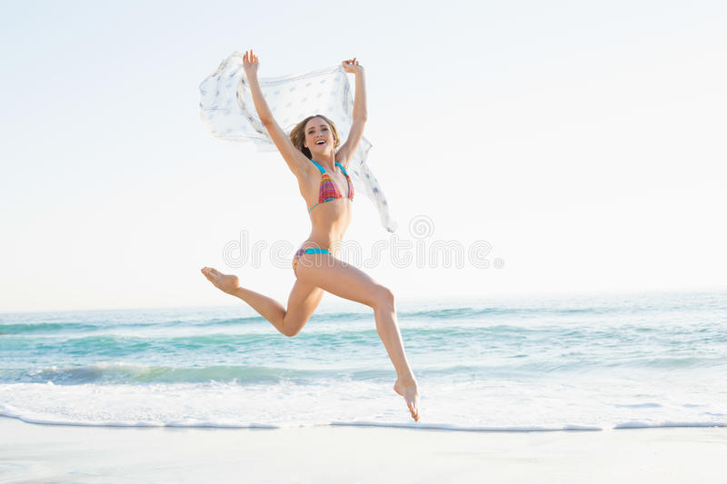 Happy slender woman jumping in the air holding shawl royalty free stock photo