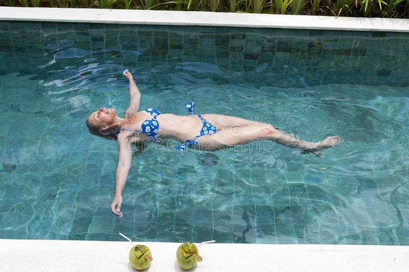 happy slender young woman lies on a water surface in the pool and has a rest stock image