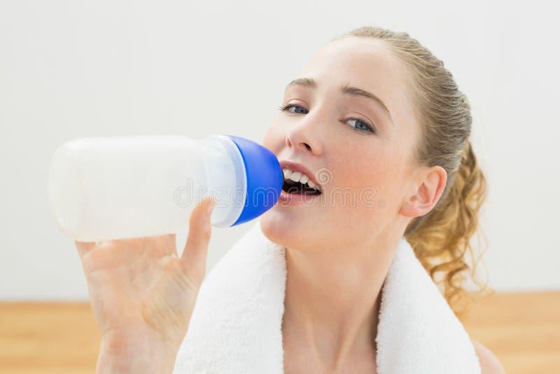 Happy slim blonde sitting on floor drinking from sports bottle stock photo
