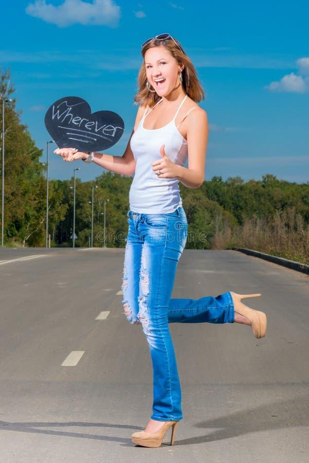 Happy slim girl hitchhiking on asphalt road. Happy slim girl hitchhiking on the asphalt road stock photo