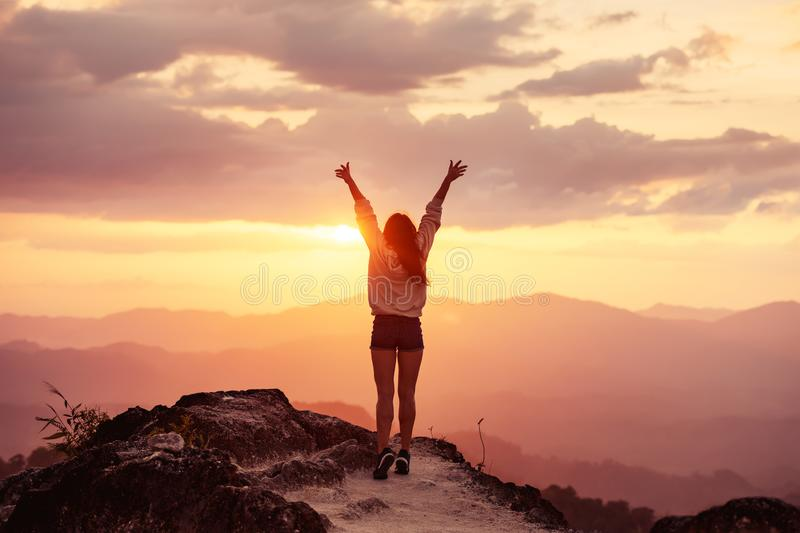 Happy slim girl at sunset mountains with raised arms royalty free stock photography