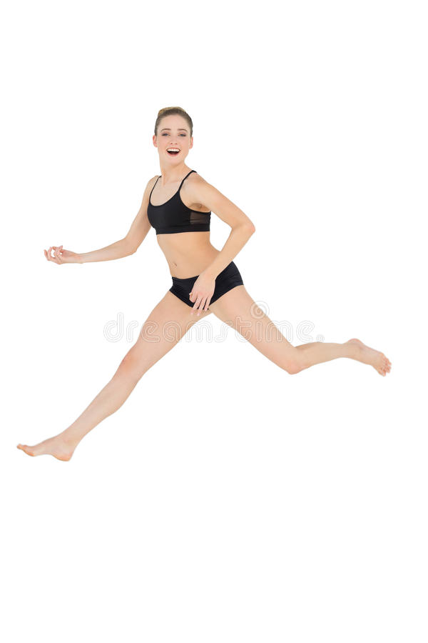 Happy slim model jumping in the air stock image