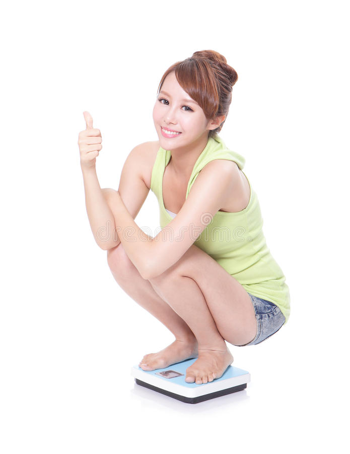 Happy slim woman with scales and show thumb up royalty free stock images