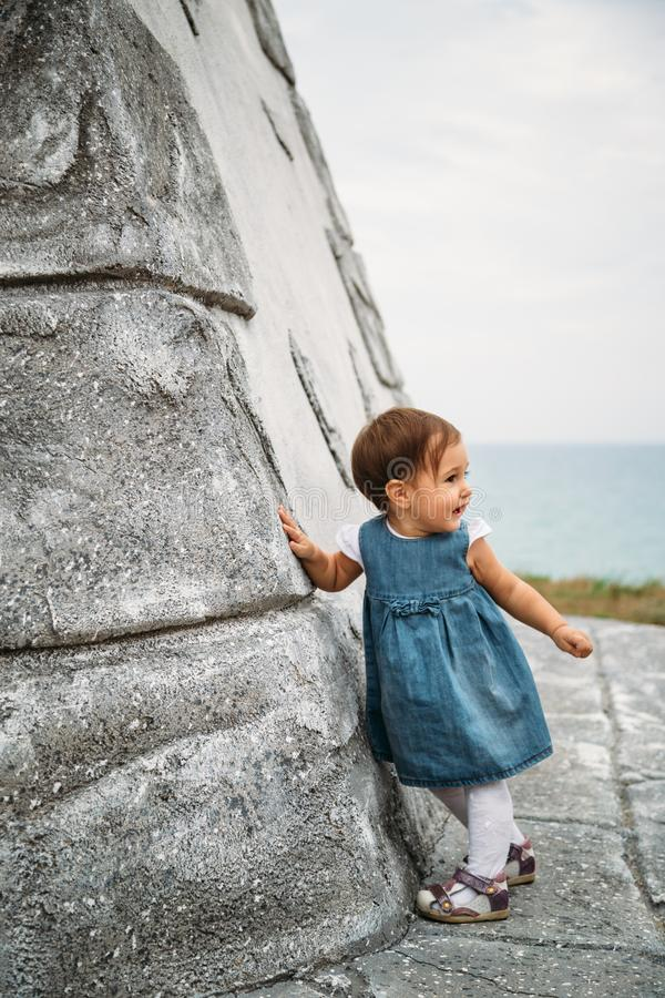 Happy small baby girl in jeans dress standing near to the wall of the old lighthouse stock images