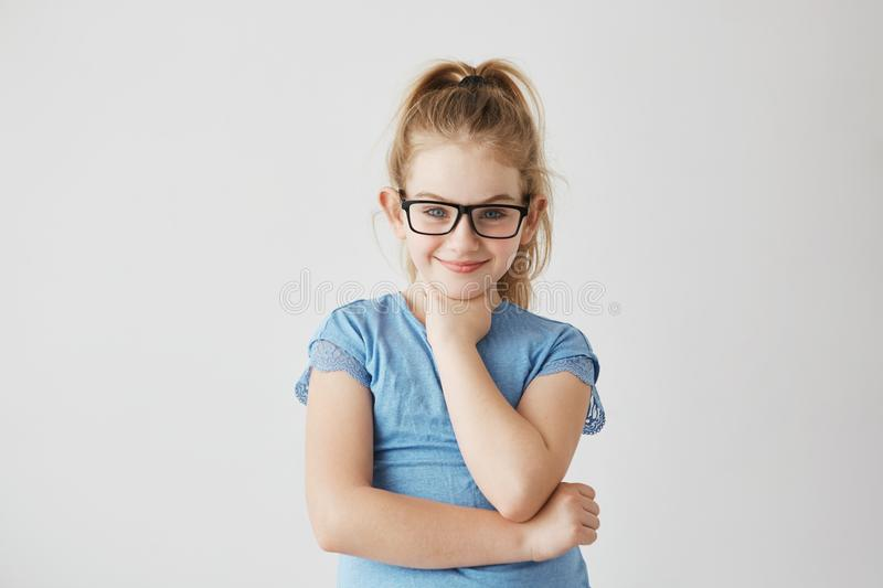 Happy small blonde girl with blue eyes looking in camera with happy and peaceful expression in brand new black glasses. royalty free stock photography