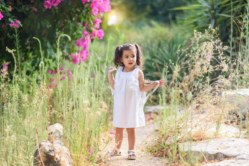 Beautiful little girl in white dress standing near pink flowers. Pretty tenderness toddler looking away. royalty free stock photos