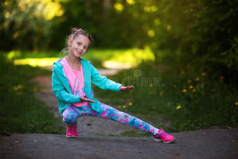Happy small child jumping active for pleasure. Active and energetic girl having fun in summer. The concept of sports, dance, hip stock photography
