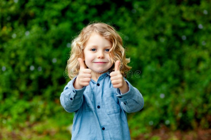 Happy small child with long blond hair and saying OK royalty free stock photography
