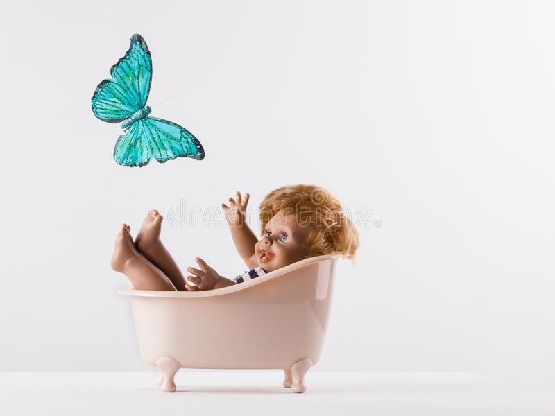 Happy small doll-boy in the bath, looking at a beautiful flying stock photography