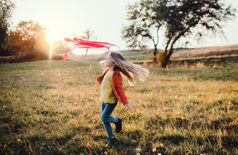 A small girl playing with a rainbow hand kite in autumn nature at sunset. stock image