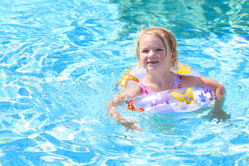 Happy small girl swimming in the pool stock photography