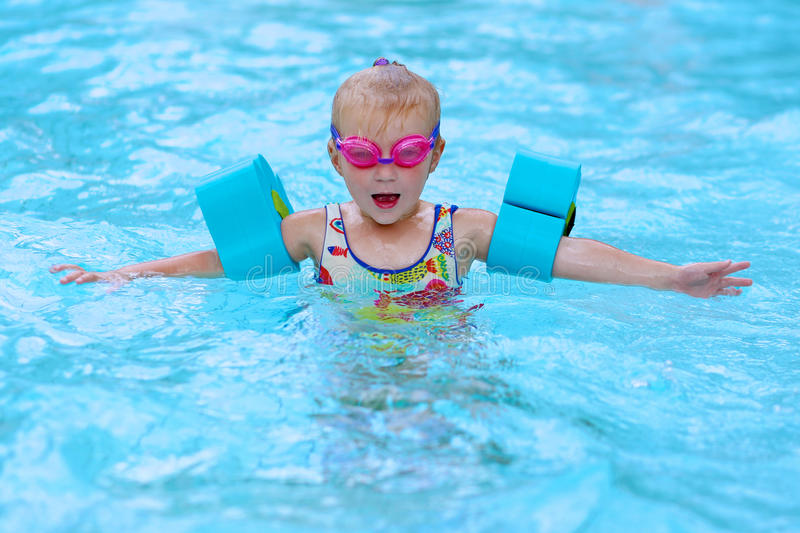 Happy small girl swimming in the pool royalty free stock image