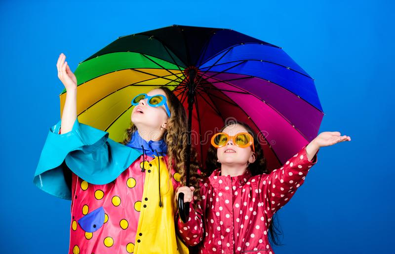 Happy small girls with colorful umbrella. autumn fashion. cheerful hipster children, sisterhood. rain protection stock image