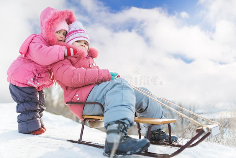 Happy small girls in pink winter clothing sledding downhill on snow royalty free stock photography