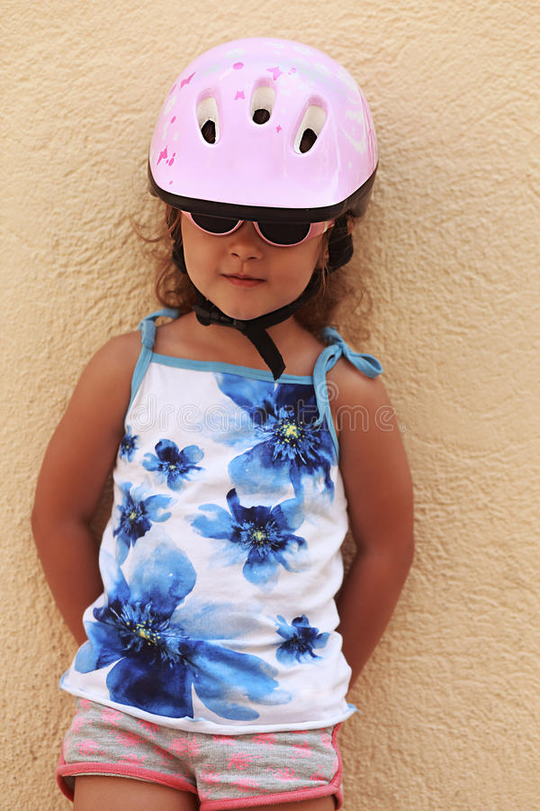 Happy small kid girl in bike helmet standing stock images