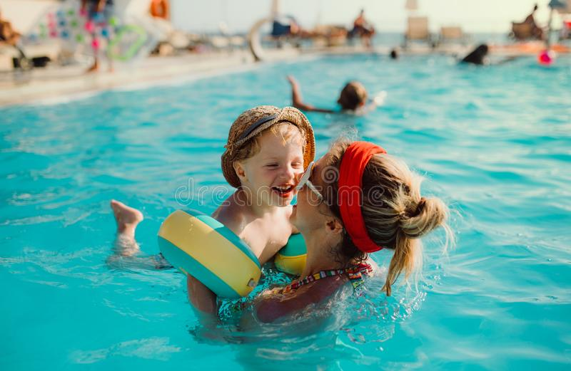 A small toddler boy with armbands and mother swimming in water on summer holiday. stock photo