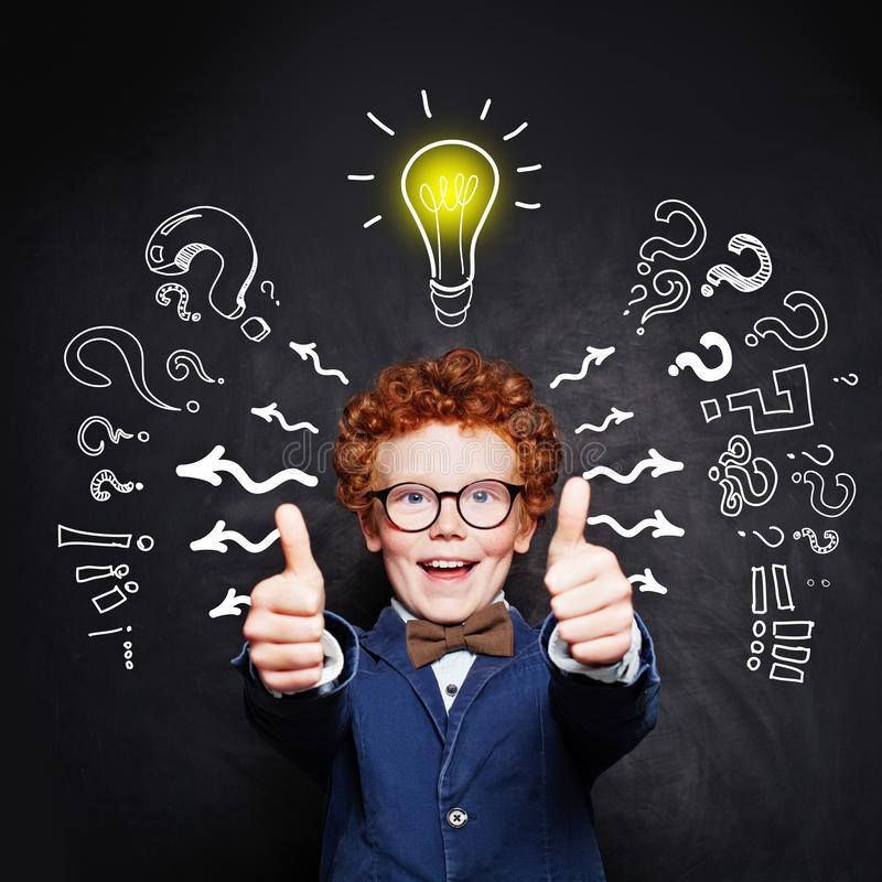 Happy smart child boy in blue suit and  lightbulb royalty free stock photo