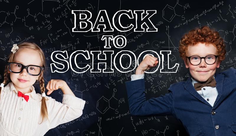 Happy smart kids in school uniform having fun on blackboard background, back to school and science power concept stock photos