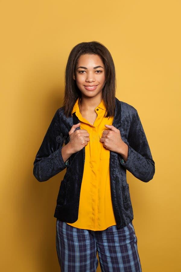 Happy smart optimistic black woman on yellow background, studio portrait royalty free stock images