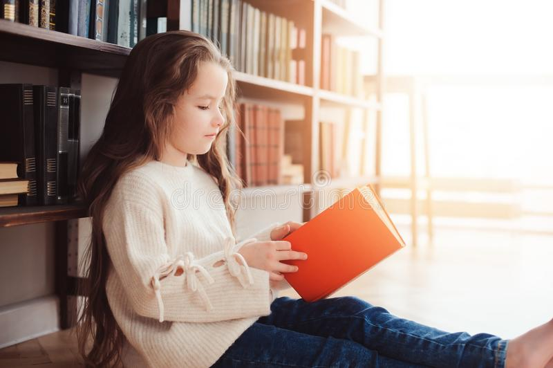 Happy smart schoolgirl reading books in library or at home stock photography