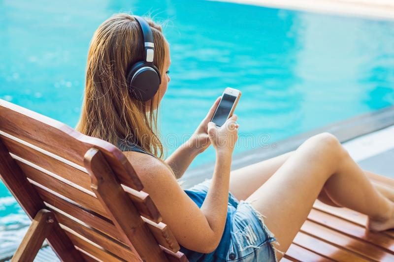 Happy smartphone woman relaxing near swimming pool listening with earbuds to streaming music. Beautiful girl using her mobile phon stock photo