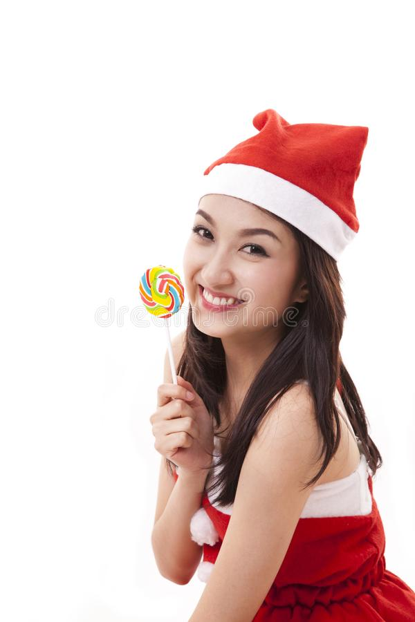 Happy smile asian girl wearing a santa suit holding a candy stock photo