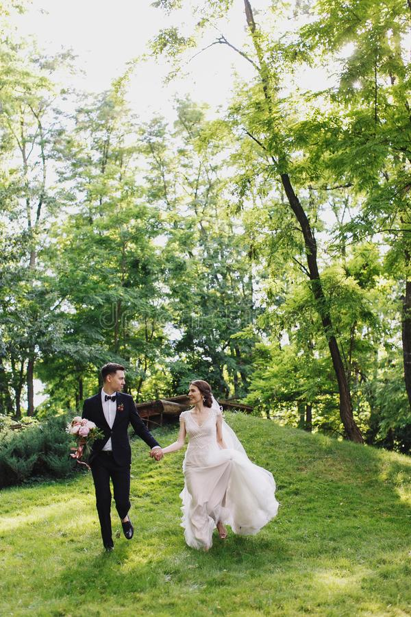 Happy smile bride and groom look at each other and running in the green garden. Wedding in the summer in the park. Happy stock photo