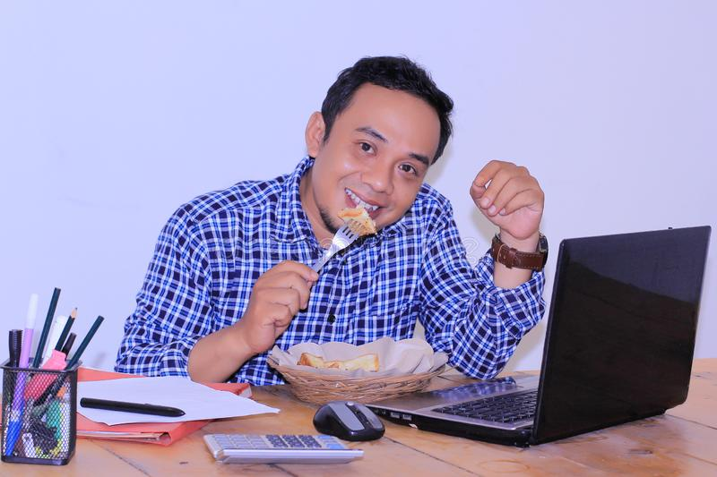 Happy smile expression an employe which enjoy his breakfast on the desk job stock photos