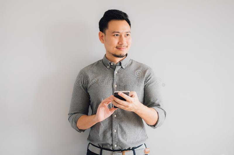 Happy smile face of handsome Asian man use smartphone stand  on gray background stock images