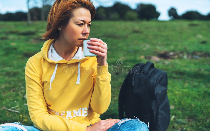 Happy smile girl holding in hands cup of hot tea on green grass in outdoors nature park, beautiful woman hipster enjoy drinking cu stock image
