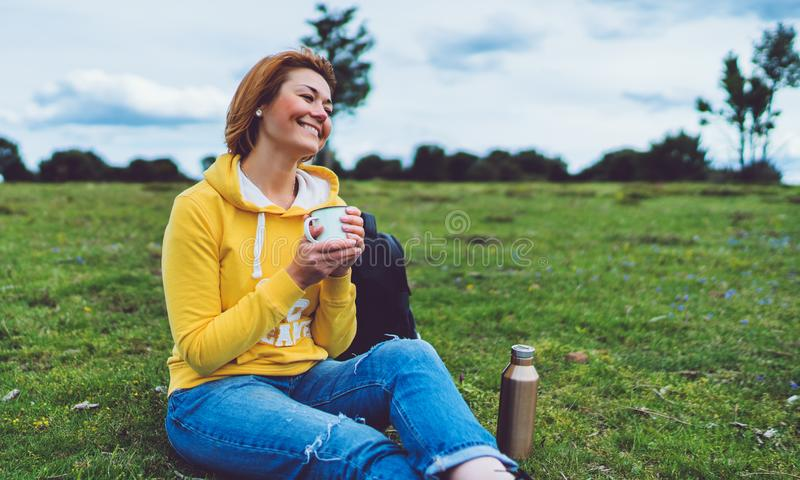 Happy smile girl holding in hands cup of hot tea on green grass in outdoors nature park, beautiful young woman hipster enjoy drink stock image