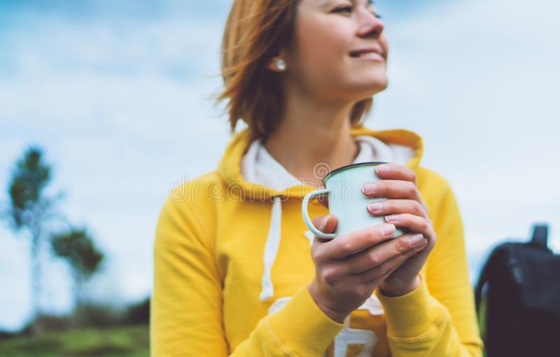 Happy smile girl holding in hands cup of hot tea on green grass in outdoors nature park, woman hipster enjoy drinking cup royalty free stock photo