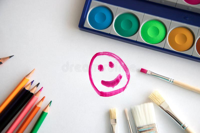 Happy smile painted with raspberry paint on a white sheet of paper with colored pencils, a box with paint and brushes for painting vector illustration