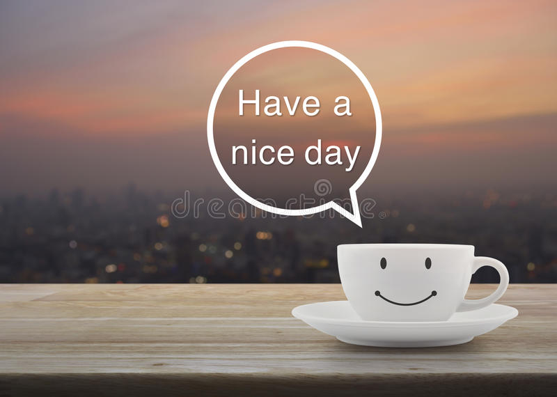 Happy smile white coffee cup on wooden table over blur cityscape on warm light sunshine, Have a nice day massage concept stock photos