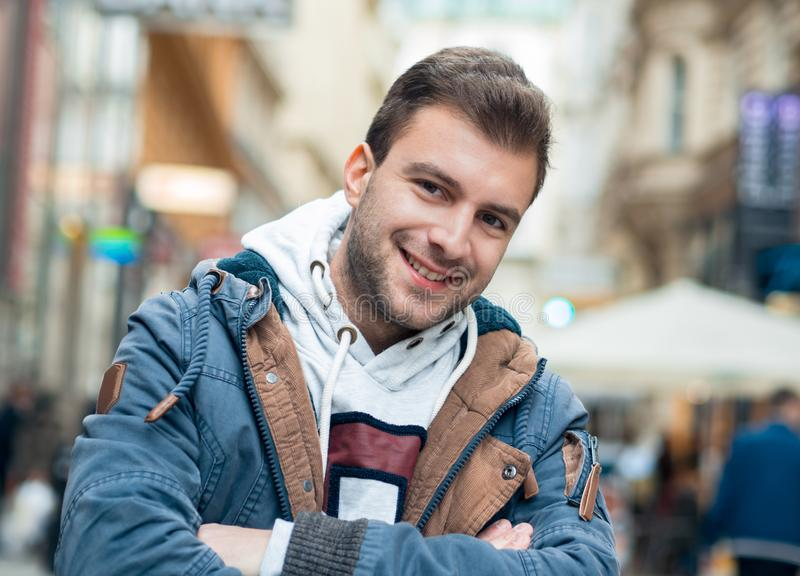 Happy smile young man. Portrait of laughing guy on the street. Outdoor, outside royalty free stock image