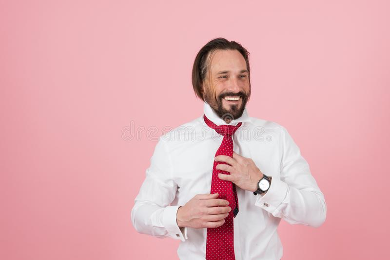 Happy smiled man in white shirt dressing on red tie. Bearded manager with red tie takes off jacket on pink background. stock photo