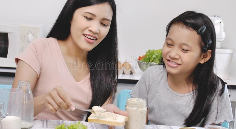 Happy smiled mother and daughter making sandwiches stock images