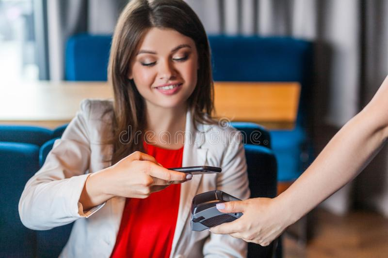 Happy smiley beautiful brunette young woman sitting with mobile smart phone and paying by pay pass pos. contactless, nfc. Technology on cellphone and payment stock photography