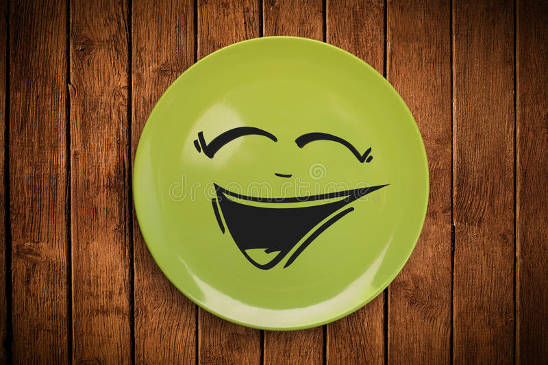 Happy smiley cartoon face on colorful dish plate. And grungy background stock image