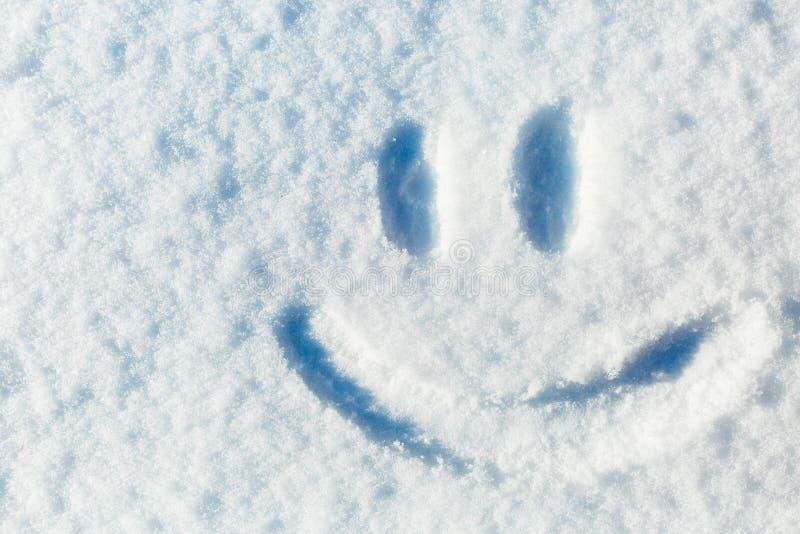 Happy smiley emoticon face in snow, winter season joy concept. Happy smiley emoticon face in snow, winter season joy and happiness concept stock images