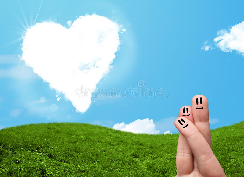 Happy smiley fingers looking at heart shaped cloud stock images