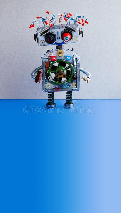 Happy smiley robot on gray blue background. Creative design steampunk toy, electric wires hairstyle. copy space royalty free stock photography