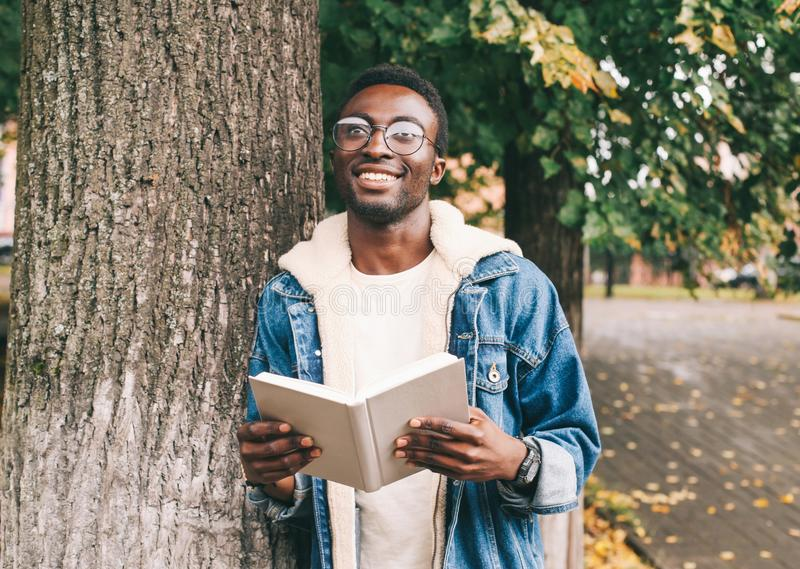 Happy smiling african man dreams, holds book in autumn. City park near tree stock images