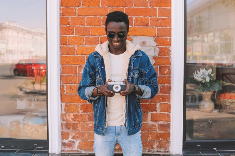 Happy smiling african man holding vintage film camera taking picture on city street over brick wall. Background royalty free stock photography