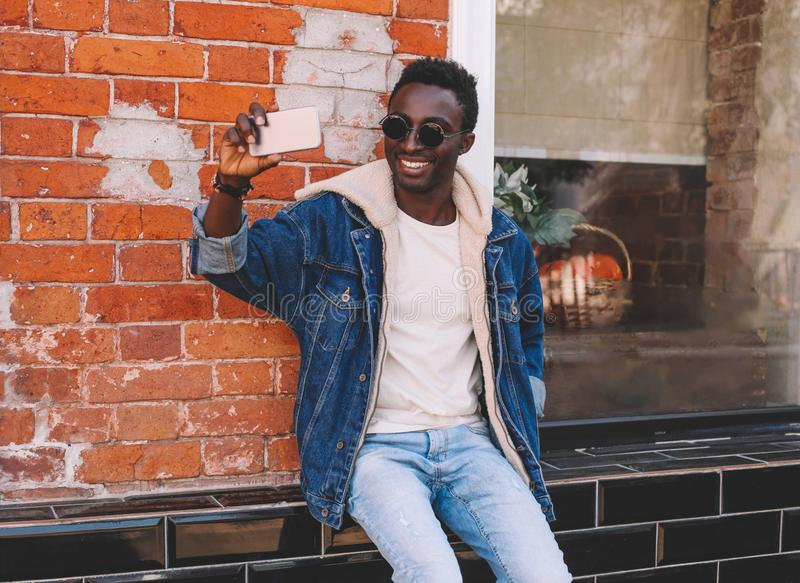 Happy smiling african man taking selfie picture by smartphone sitting on city street over brick textured wall. Background royalty free stock photography