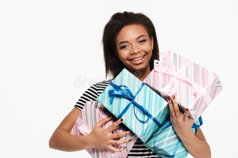 Happy smiling african woman holding stack of present boxes royalty free stock images