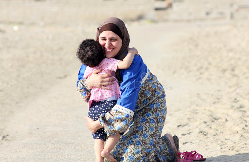 Happy smiling arab muslim mother hug her baby girl stock images