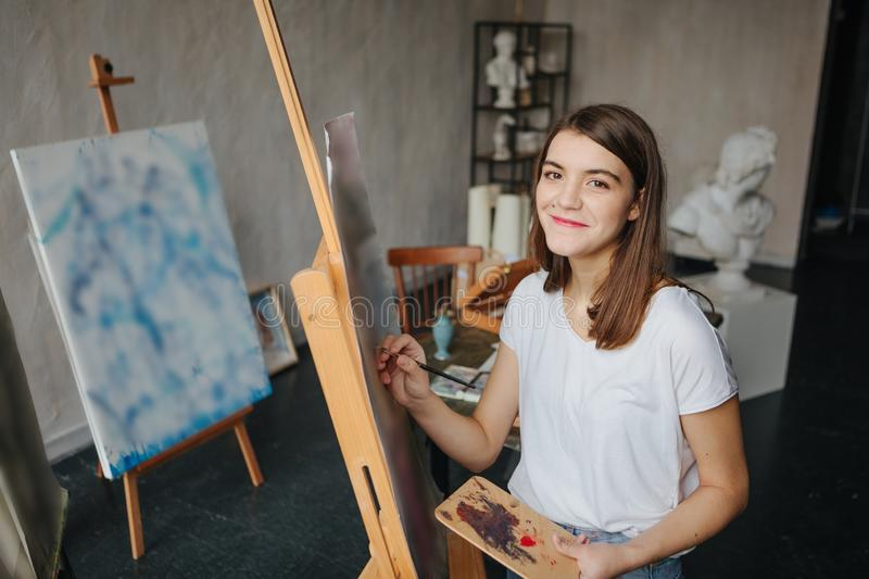 Happy smiling Artist painter young beautiful girl. Working creating process. painting on easel. inspired work. Horizontal composition. Adorable young student stock photography